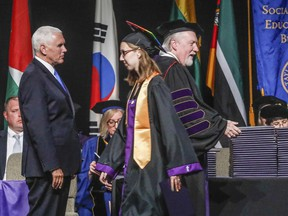 Taylor University student, Laura Rathburn receives her diploma from Taylor University President Paul Lowell Haines as she walks past Vice President Mike Pence, left, during the commencement ceremony Saturday, May 18, 2019 in Upland, Ind. Dozens of graduates and faculty have protested the selection of Vice President Mike Pence as the commencement speaker at Taylor University in Indiana by walking out moments before his introduction.