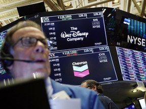 FILE - In this April 12, 2019, file photo the logos for The Walt Disney Company and Chevron appear above a trading post on the floor of the New York Stock Exchange. The Walt Disney Company reports financial results Wednesday, May 8.