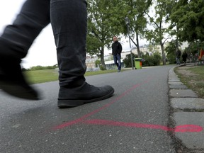 A man walks past a so called 'Drug Dealer Area' next to a traffic training course for kids at the public Goerlitzer Park in Berlin, Germany, Thursday, May 9, 2019.
