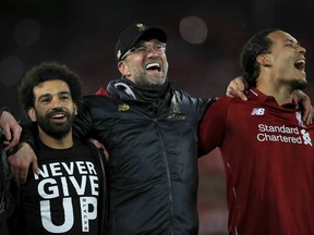 Liverpool's Mohamed Salah, left, manager Jurgen Klopp, center, and Virgil van Dijk celebrate after the Champions League Semi Final, second leg soccer match between Liverpool and Barcelona at Anfield, Liverpool, England, Tuesday, May 7, 2019. Liverpool won the match 4-0 to overturn a three-goal deficit to win the match 4-3 on aggregate.
