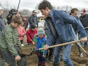 Wearing a Stelco jacket, Prime Minister Justin Trudeau fills sandbags with son Xavier as son Hadrien watches, in Constance Bay on Saturday, April 27, 2019.