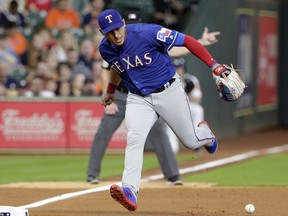 Texas Rangers third baseman Asdrubal Cabrera (14) loses the ball on the infield grounder by Houston Astros George Springer during the first inning of a baseball game Thursday, May 9, 2019, in Houston.