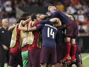 Arsenal players celebrate after forward Alexandre Lacazette scoried his side's second goal during the Europa League semifinal soccer match, second leg, between Valencia and Arsenal at the Camp de Mestalla stadium in Valencia, Spain, Thursday, May 9, 2019.