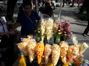 FILE - In this July 5, 2016 file photo, a street vendor sells fried snacks packaged in plastic bags in Mexico City. Mexico City lawmakers announced on Thursday, May 9, 2019 they have passed a ban on plastic bags, utensils and other disposable plastic items to take effect at the end of 2020, giving businesses more than a year to make the switch to biodegradable products.