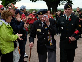 Richard Brown, a Canadian veteran of the Battle of Normandy, departs with his son Andy to the applause of visitors following a commemorative ceremony at the Commonwealth War Graves Commissions Beny-sur-Mer Canadian War Cemetery in Normandy on June 5, 2019, near Reviers, France.