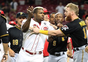 Yasiel Puig #66 of the Cincinnati Reds is restrained during a bench clearing altercation in the 9th inning of the game against the Pittsburgh Pirates at Great American Ball Park on July 30, 2019 in Cincinnati, Ohio.