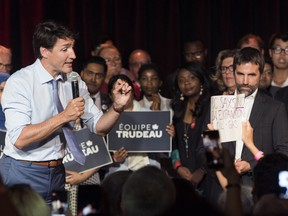 Prime Minister Justin Trudeau, left, addresses a protester during an event in Montreal, Wednesday, July 10, 2019, where Steven Guilbeault, right, launched his candidacy to run in the upcoming federal election for the Liberal party of Canada in the Montreal riding of Laurier-Sainte-Marie.