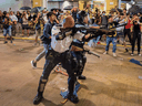 A riot police officer holds a shotgun towards protestors during a demonstration on July 30, 2019 in Hong Kong.