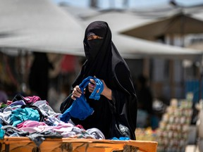 A Syrian woman picks clothes in the al-Hol camp in al-Hasakeh governorate in northeastern Syria, on August 08, 2019.