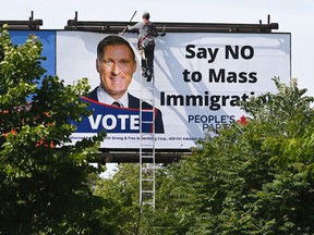 """A worker removes a billboard featuring the portrait of PeopleÕs Party of Canada (PPC) leader Maxime Bernier and its message """"Say NO to Mass Immigration"""" in Toronto, Ontario, Canada August 26, 2019."""