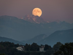 A near full moon rises behind The French Alps as seen from Geneva on September 12, 2019.