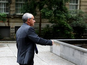 Shaun Rootenberg, alias Shaun Rothberg, tries to avoid a photographer outside Superior Court in Toronto on Thursday, Sept. 12, 2019. Rootenberg was found guilty in July of defrauding a woman he had met on the internet of $595,000 by diverting funds she gave him to invest for her. He is seeking a mistrial before sentencing.