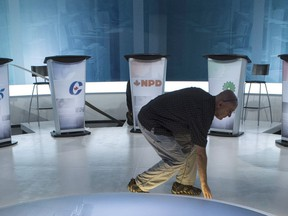 A campaign that could start at any time and a debating schedule that is itself the subject of debate are intesifying pre-election jitters in Ottawa going into the weekend. A technician cleans the set in preparation for Thursday night's French language leaders debate in Montreal, Wednesday, Sept. 23, 2015.