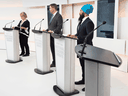Green Party Leader Elizabeth May, Conservative Leader Andrew Scheer and NDP Leader Jagmeet Singh, along with an empty lectern where Liberal Leader Justin Trudeau would have been, at the first leaders' debate on Sept. 12, 2019 in Toronto.