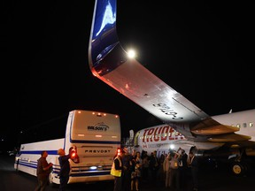 Members of the media inspect the wing from Liberal Leader Justin Trudeau's campaign plane after being struck by the media bus following landing in Victoria, B.C., on Wednesday, Sept.11, 2019.
