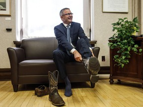 Alberta Finance Minister Travis Toews puts on a pair of cowboy boots during a pre-budget photo op in Edmonton on Wednesday, Oct. 23, 2019.