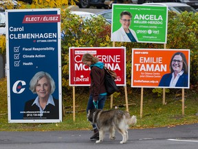 A woman walks her dog past federal candidate election signs in the riding of Ottawa Centre on Oct. 16, 2019.