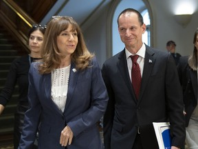 Quebec Finance Minister Eric Girard, right and Quebec Culture and Communications Minister Nathalie Roy walk to a news conference to announce measures to help media, Wednesday, October 2, 2019 at the legislature in Quebec City.