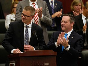 Alberta Finance Minister Travis Toews, left, is applauded by Premier Jason Kenney after Toews delivered his budget at the Alberta Legislature in Edmonton on Oct. 24, 2019.