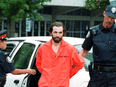 """Steven Guilbeault is taken into custody by Toronto police after scaling the CN Tower in July 2001. """"To me, civil disobedience was never a goal in and of itself. It was just a tool,"""" Guilbeault now says."""