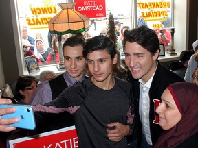 A Syrian family sponsored by the community take a selfie with Liberal Leader Justin Trudeau during a campaign stop in Tilbury, Ont., on Oct. 15, 2019. From left to right are Hamid Alhajjeh, 19, his brother Mulham Allajjeh, 18, and their mother Noura Alchreifi.