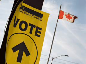 "An Elections Canada ""vote"" sign is seen next to a Canadian flag."