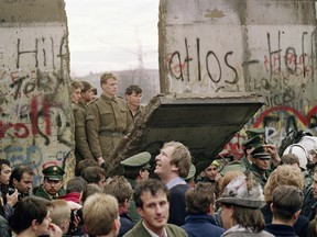 West Berliners crowd in front of the Berlin Wall early 11 November 1989 as they watch East German border guards demolishing a section of the wall in order to open a new crossing point between East and West Berlin, near the Potsdamer Square.