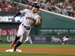Jose Altuve #27 of the Houston Astros rounds third base and scores a run on a hit by Alex Bregman against the Washington Nationals during the first inning in Game Four of the 2019 World Series at Nationals Park on October 26, 2019 in Washington, DC.