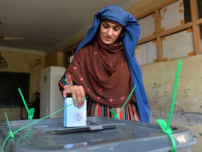 A woman casts her vote for the presidential election at a polling station in Jalalabad, Afghanistan, on Sept. 28, 2019.