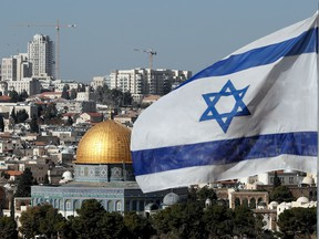 The Israeli flag flutters in front of the Dome of the Rock mosque and the city of Jerusalem.