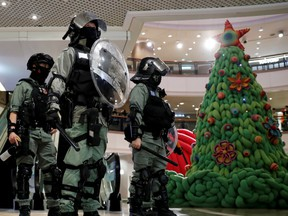 Riot police stand guard next to a Christmas tree inside a shopping mall during an anti-government protest on Christmas Eve at Tsim Sha Tsui in Hong Kong, China, December 24, 2019.