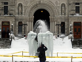 A man takes a photo of a frozen fountain outside the B.C. Legislature in Victoria, B.C.,  on Jan. 15, 2020.