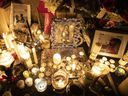 Photographs are left among candles at a memorial during a vigil in Toronto on Thursday, January 9, 2020, to remember the victims of the Iranian air crash.