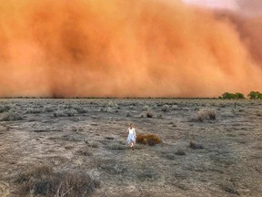 A child runs towards a dust storm in Mullengudgery in New South Wales on Jan. 17.