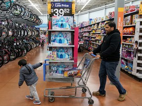 A boy and his father walk through the toy section of a Walmart in King of Prussia, Penn., on Black Friday, Nov. 29, 2019.