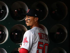 Mookie Betts #50 of the Boston Red Sox stands in the dugout before their game against the Oakland Athletics at Oakland-Alameda County Coliseum on April 03, 2019 in Oakland, California.
