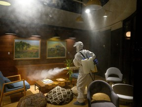 A worker wearing a protective suit uses a fogging machine to disinfect a business establishment in Shanghai on Feb. 9, 2020.