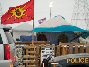 Ontario Provincial Police and First Nations protesters sit on opposite sides of a barricade on Highway 6 near Caledonia, Ont., which the protesters set up in support of Wet'suwet'en hereditary chiefs, on Feb. 26, 2020.