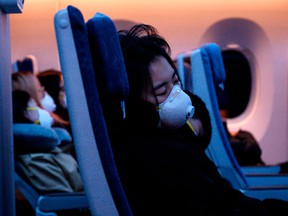 Passengers wearing protective face masks sleep on their flight to Shanghai on Tuesday.