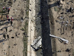 In this Jan. 8, 2020 photo, rescue workers search the scene where a Ukrainian plane crashed in Shahedshahr, southwest of the capital Tehran, Iran.