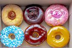 Top view Inside of a Tim Hortons six donuts box, with a: Dulce de Leche, Chocolate Truffle, Strawberry, Vanilla Dip, Chocolate, Maple Dip Donut.