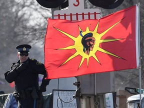 An Ontario Provincial Police officer talks on a radio after arrests were made at a rail blockade in Tyendinaga Mohawk Territory, near Belleville, Ont., on Feb. 24, 2020.