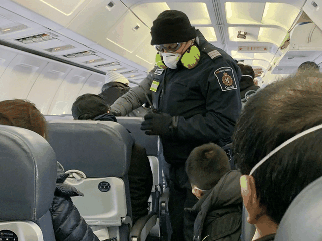 An RCMP officer checks Canadians one their way to quarantine at CFB Trenton, after being evacuated from China due to the coronavirus outbreak, Feb. 7, 2020. Courtesy of Edward Wang via Reuters