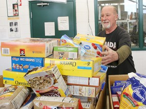 A man sorts through food items at the Sudbury Food Bank in Sudbury, Ont., on March 18. What happens when all the elderly and sick volunteers stay home?