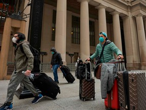 Travellers in masks leave Union Station in Toronto, Ontario on March 24, 2020.