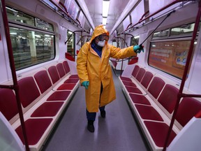 An employee wearing protective gear sprays disinfectant to sanitize a tube train over coronavirus fears in Tbilisi, Georgia March 2, 2020.