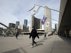 A small group of pedestrians pass through Nathan Phillips Square in front of Toronto City Hall as Torontonians adjust to the new normal.