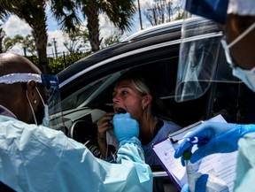 "A medical personnel member takes samples of Lee Dinzik at a ""drive-thru"" coronavirus testing lab set up by a local community centre in West Palm Beach, north of Miami, on March 16, 2020."