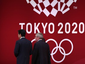 In this file photo taken on July 24, 2019 International Olympic Committee president Thomas Bach (R) walks with Japan's Prime Minister Shinzo Abe (L) as they leave the stage during a ceremony marking one year before the start of the Tokyo 2020 Olympic Games in Tokyo.