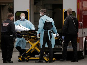 Medics prepare to transfer a patient to an ambulance from a long-term care facility linked to two confirmed coronavirus cases in Kirkland, Wash., on March 1, 2020.